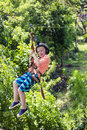 Happy smiling little boy riding a zip line in a lush tropical forest Royalty Free Stock Photo