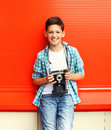 Happy smiling little boy teenager with retro vintage camera Royalty Free Stock Photo