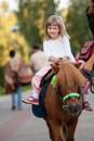 Happy smiling little girl  on a pony Royalty Free Stock Photo