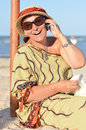 Happy smiling looking at camera mature woman sitting on beach and talking on mobile phone outdoors Stock Photos