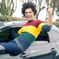 Happy smiling man with new car holding key sitting out of window of Stock Photo