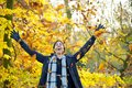 Happy smiling man throwing leaves with open arms in autumn portrait of a Stock Images