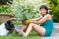 Happy smiling middle age woman gardening offsets the flowers in a pot Stock Image