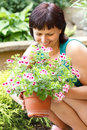 Happy smiling middle age woman gardening offsets the flowers in a pot Stock Photography