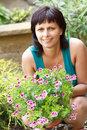 Happy smiling middle age woman gardening offsets the flowers in a pot Stock Photos