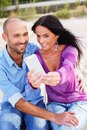 Happy smiling middle aged couple on a beach taking photo of themselves Royalty Free Stock Photography