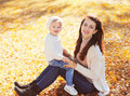 Happy smiling mom with little child playing in autumn park Royalty Free Stock Photo
