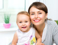 Happy smiling mother and baby kissing hugging at home Royalty Free Stock Photos