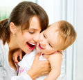 Happy smiling mother and baby kissing hugging at home Stock Images