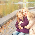 Happy smiling mother and daughter outdoor near lake. Royalty Free Stock Photo