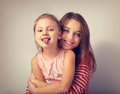 Happy smiling mother hugging with love her frolic grimacing kid Royalty Free Stock Photo