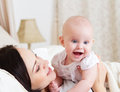 Happy smiling mother with six month old baby girl indoor Stock Photo