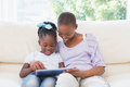 Happy smiling mother using tablet with her daughter on couch in living room Royalty Free Stock Photography