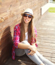 Happy smiling pretty young woman wearing a pink shirt and summer hat sitting resting in city Royalty Free Stock Photo