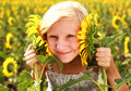 Happy smiling teen girl playing with sunflower in field Royalty Free Stock Photo