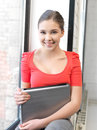 Happy and smiling teenage girl with laptop bright picture of Royalty Free Stock Photo