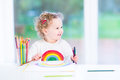 Happy smiling toddler girl drawing a rainbow Royalty Free Stock Photo
