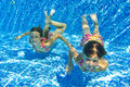 Happy smiling underwater children in swimming pool Stock Photography