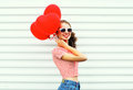 Happy smiling woman with air balloons heart shape having fun over white