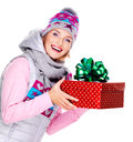 Happy smiling woman giving a christmas gift photo of adult in winter outerwear isolated on white Stock Image