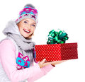 Happy smiling woman giving a christmas gift photo of adult in winter outerwear isolated on white Royalty Free Stock Photos