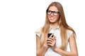Happy smiling woman holding a mobile phone looking away isolated on white background Stock Photo