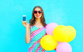 Happy smiling woman shows smartphone holding an air colorful balloons