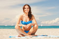 Happy smiling woman sitting on a towel picture of Royalty Free Stock Images