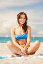 Happy smiling woman sitting on a towel picture of Royalty Free Stock Photography