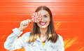 happy smiling woman with sweet caramel lollipop over colorful orange background Royalty Free Stock Photo