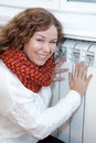 Happy smiling woman touching warm heating con Royalty Free Stock Photo