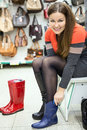 Happy smiling woman wearing rubber boots in shop the Stock Photo