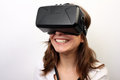 Happy smiling woman in a white shirt wearing oculus rift vr virtual reality d headset laughing intrigued formal an and exploring Stock Image