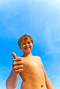 Happy smiling young boy with background blue sky gives fingersign all right thumbs up Royalty Free Stock Photography