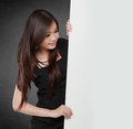 Happy smiling young business woman showing blank signboard isolated on black background Stock Photos