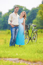 Happy and smiling young caucasian couple having romantic time to together in the park with bicycle vertical image Royalty Free Stock Images