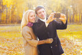 Happy smiling young couple together taking picture self portrait on smarphone in sunny autumn