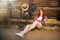 Happy smiling young cowgirl resting at the ranch fence Royalty Free Stock Photo