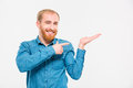 Happy smiling young man with beard holding copyspace on palm and pointing it over white background Stock Images
