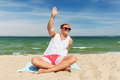 Happy smiling young man sunbathing on beach towel Royalty Free Stock Photo