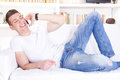 Happy smiling young man talking on mobile relaxing at home sofa Royalty Free Stock Photography