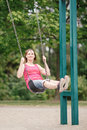 Happy smiling young middle age woman girl in red tshirt and jeans shorts on swing on backyard playground Royalty Free Stock Photo