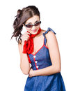Happy smiling young pinup girl in rockabilly style with smile wearing a red and blue dress with neckerchief and sunglasses studio Stock Images