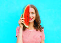 Happy smiling young woman is closing half face with slice of watermelon Royalty Free Stock Photo