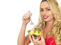 Happy smiling young woman eating fresh fruit salad attractive worth long blonde hair in her twenties looking at the camera and Royalty Free Stock Image