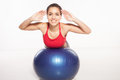 Happy smiling young woman exercising her abs on a pilates ball lying stretched out over the top with her hands raised looking at Stock Photography