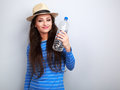 Happy smiling young woman holding bottle of pure water on blue b Royalty Free Stock Photo