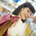 Happy smiling young woman holding shopping bags indoors in store Stock Image