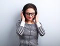 Happy smiling young woman listening the music from headphones on blue background Stock Image