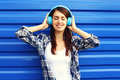 Happy smiling young woman listens and enjoys the music in headphones over blue background Stock Photos